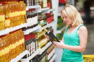 woman choosing bio food olive oil in grocery shopping store